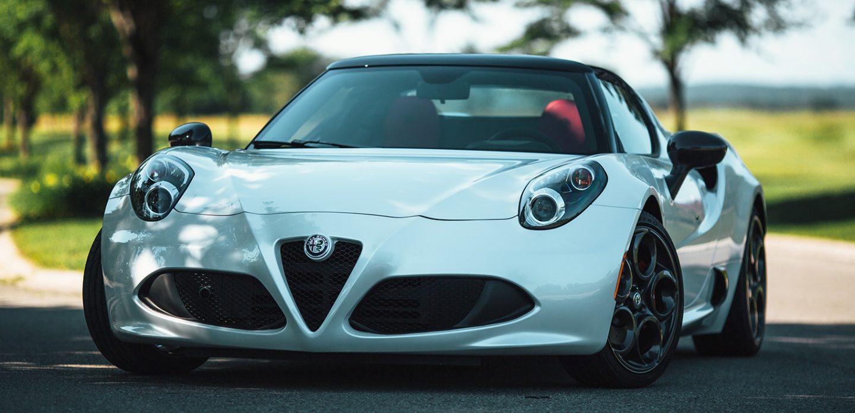 Se muestra una vista frontal de perfil del Alfa Romeo 4C Spider 2019 estacionado en un área recreativa.