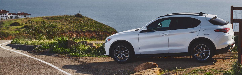 Un Alfa Romeo Stelvio Ti 2019 estacionado en una colina con vista hacia el océano.
