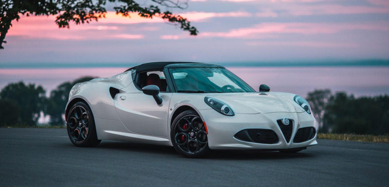 Se muestra una vista frontal de perfil del Alfa Romeo 4C Spider 2020 estacionado cerca del agua al atardecer.