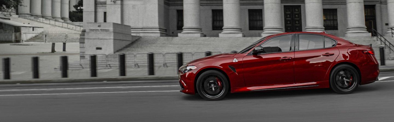 UnAlfa Romeo Giulia Quadrifoglio2020 en rojo, estacionado en una calle de ciudad junto a un edificio señorial con grandes columnas.