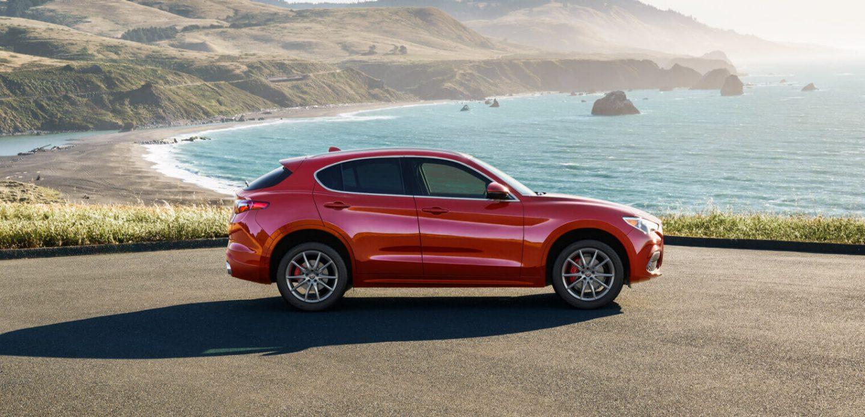 Mostrar ElAlfa Romeo Stelvio2020 estacionado junto a una playa estrecha.