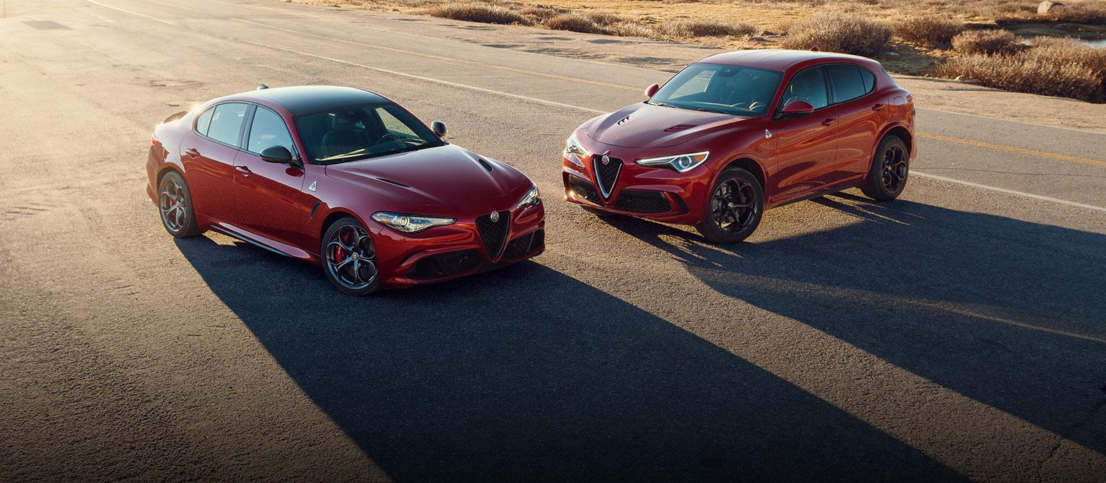 UnAlfa Romeo Giulia Quadrifoglio2021 rojo y unAlfa Romeo Stelvio Quadrifoglio2021 rojo estacionados en el borde de una carretera.