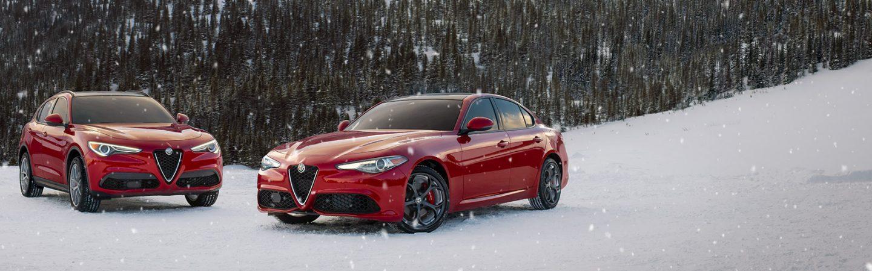 UnAlfa Romeo Giulia Ti Sport 2019 y un Alfa Romeo Stelvio Ti Sport2019, ambos rojos, estacionados en el bosque nevado.