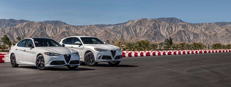 Un Alfa Romeo Giulia Ti Sport y Alfa Romeo Stelvio Quadrifoglio 2020 estacionados uno al lado de otro en una pista cerca de las montañas.