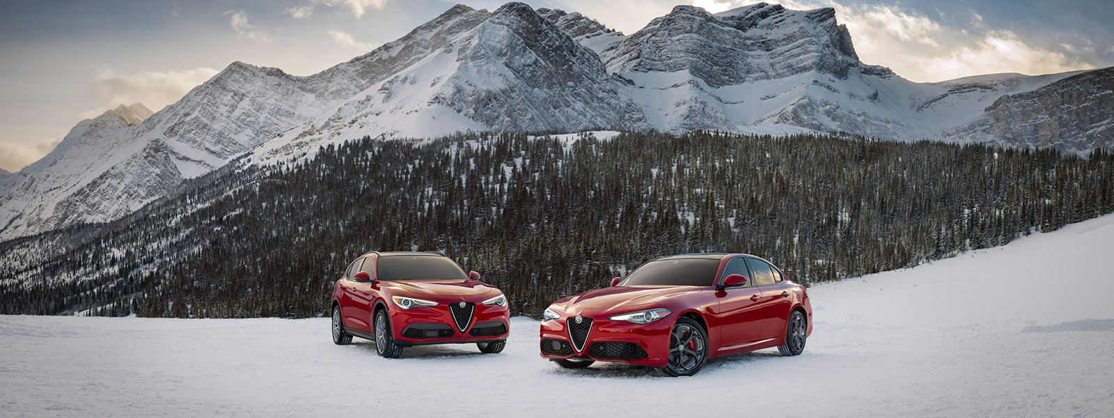 UnAlfa Romeo Giulia Ti2020 y unStelvio Ti2020 estacionados en una montaña cubierta de nieve.