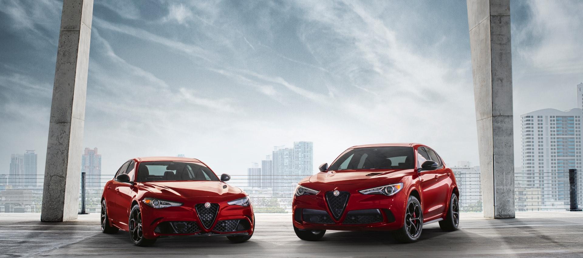 La línea Alfa Romeo, unGiulia Quadrifoglio rojo, un4C Spider blanco y unStelvio Quadrifoglio rojo estacionados en el techo de un garaje.