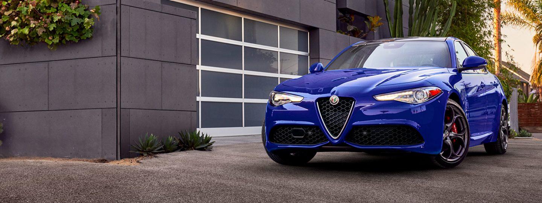 Un Alfa Romeo Giulia 2020 estacionado afuera de un edificio.