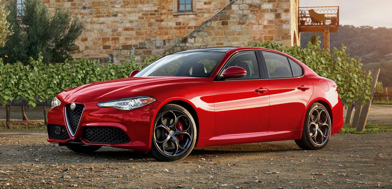 Se muestra una vista frontal de perfil del Alfa Romeo Giulia 2019 estacionado al lado de un edificio en una zona rural.